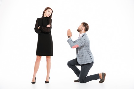 Image of offended young loving couple standing isolated over white background. Looking aside. Man ask for apologize. Stock Photo - 78517036