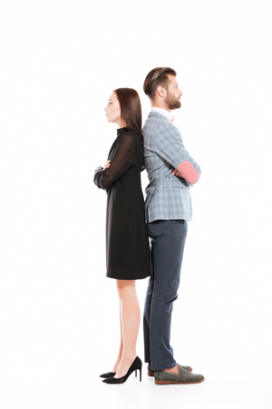 Photo of young offended loving couple standing isolated over white background. Looking aside.
