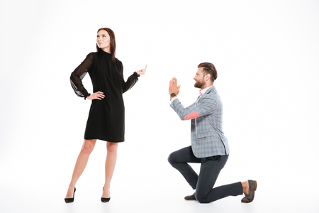 Picture of offended young loving couple swear isolated over white background. Looking aside. Man ask for apologize while woman showing middle finger.