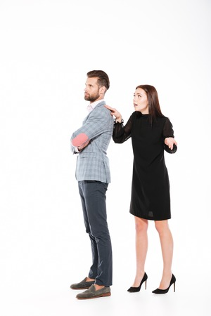 Picture of offended young loving couple swear isolated over white background. Looking aside. Woman ask for apologize. Stock Photo