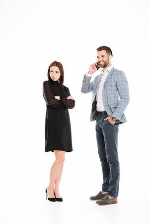 Picture of sad offended woman looking aside while man talking by phone isolated over white background.