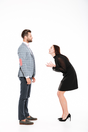 Image of offended young loving couple swear isolated over white background. Looking aside. Stock Photo - 78478053