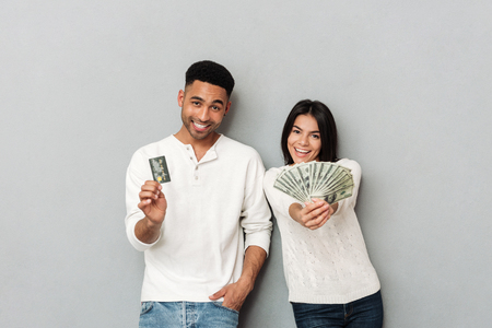 paying: Cheerful woman and african man showing credit card and cash isolated