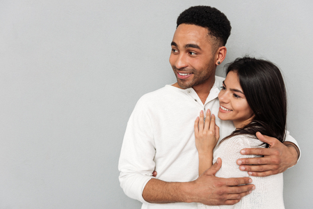 Young smiling african man hugging pretty woman while yhey looking away isolated Stock Photo