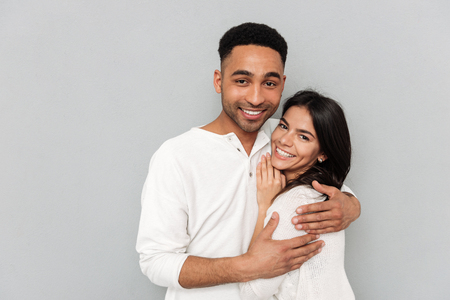 Young smiling african man hugging pretty woman isolated