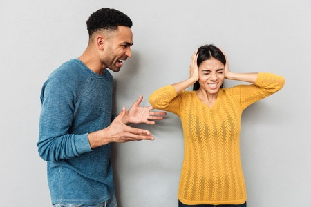 African agressive man shouting at his woman while she closing ears isolated over grey background Stock Photo - 78572693