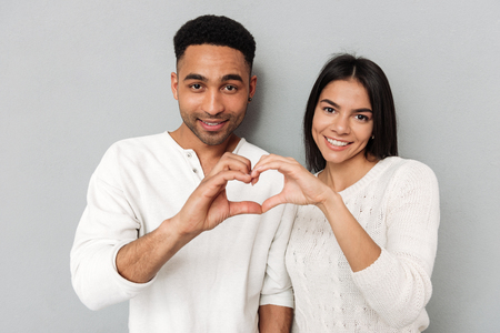 Young pretty smiling couple showing heart with hands iolated
