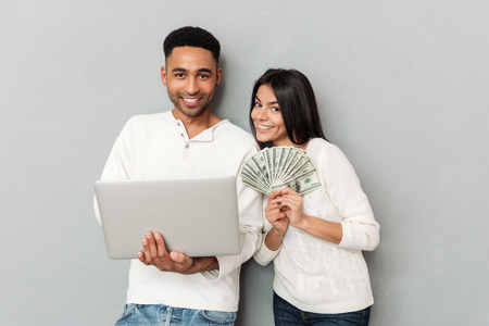 paying: Young smiling african man using laptop while his woman holding fan of money isolated Stock Photo