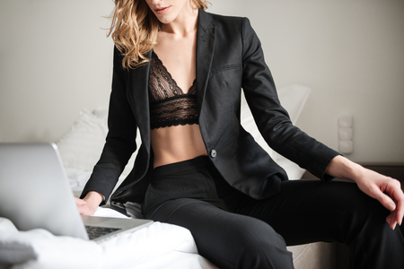 Cropped photo of sexy woman sitting on bed dressed in lingerie. Chatting by laptop computer. Stock Photo