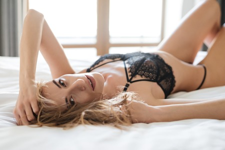 Image of sexy woman lies on bed indoors dressed in lingerie. Looking at camera. Stock Photo