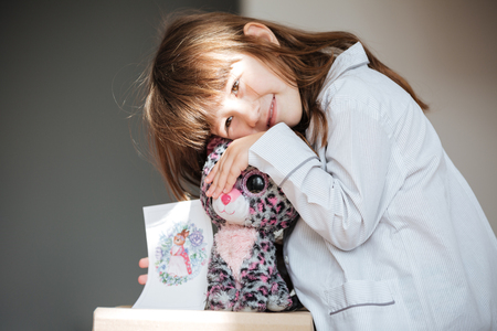 Smiling girl hugging toy and showing postcard