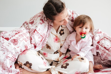 Young womam mother sitting in bed in blanket with her cute daughter