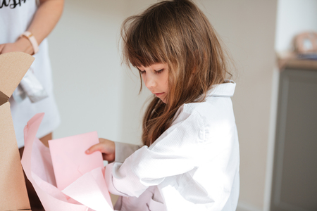 Cute child girl holding papers from delivery in hands in the morning