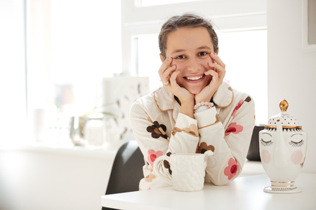 Smiling young woman wearing pajamas sitting in kitchen Stock Photo