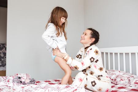 Careful mother wearing her smiling daughter while sitting in bed