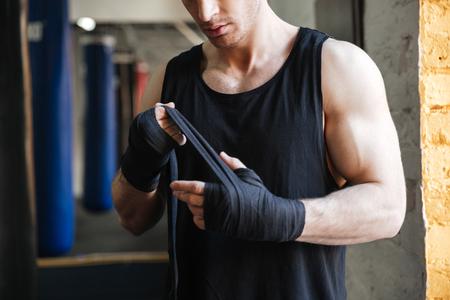 ジムでボクシングの黒い手袋を着用して強い男のイメージをトリミング 写真素材