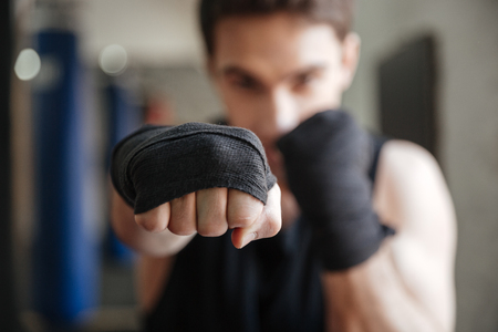 체육관에서 운동을 하 고 젊은 권투 선수의 뷰를 닫습니다. 손에 집중