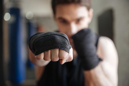 Sluit omhoog mening van een jonge bokser die oefening in gymnastiek doet. Focus op de hand