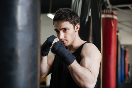 Portrait of boxer trying to kick with his hand punching bag in gym Stock Photo