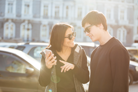 Picture of cheerful young woman walking outdoors with her brother. Looking aside using mobile phone.