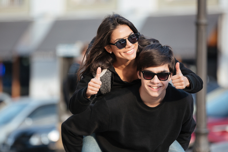 Image of young happy woman walking and have fun outdoors with her brother. Looking at camera showing thumbs up.