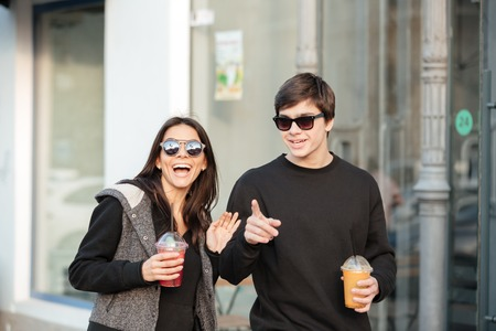 Image of happy young lady walking outdoors with her brother drinking juice. Looking aside.