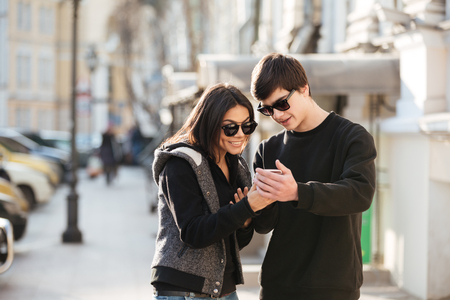 Image of happy young woman walking outdoors with her brother. Looking aside using mobile phone.