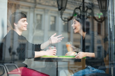 Image of smiling young man sitting in cafe with his sister drinking juice. Looking aside. Stock Photo