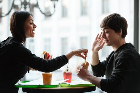 Jonge leuke vrouw die hamburger van haar broer probeert te eten terwijl zij dichtbij venster in koffie zitten Stockfoto