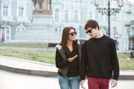Image of happy young lady walking outdoors with her brother. Looking aside.