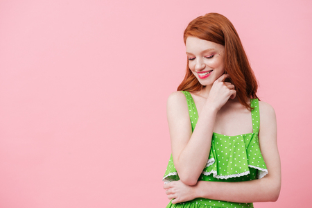 Portrait of young redhead woman wearing green dress and looking down