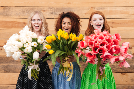 Three happy women in dresses posing near the wooden wall and showing bouquets of flowers at the camera