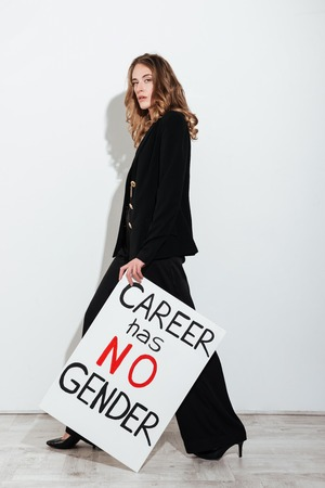 blanks: Image of amazing young caucasian lady posing over white wall while holding blank with text about gender. Looking at camera. Stock Photo