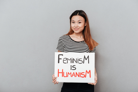 Smiling asian feminist woman holding poster with slogan Feminism is humanism isolated Фото со стока