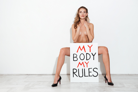 Full-length shot of naked woman feminist holding nameplate My body my rules