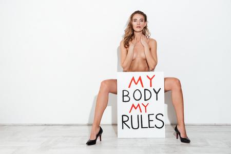 Full-length tiro de mulher nua segurando placa de identificação 'meu corpo minhas regras'