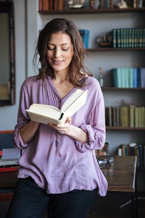 Retrato de un sonriente libro de lectura casual mujer madura mientras se inclina sobre el escritorio en el interior Foto de archivo - 79084151