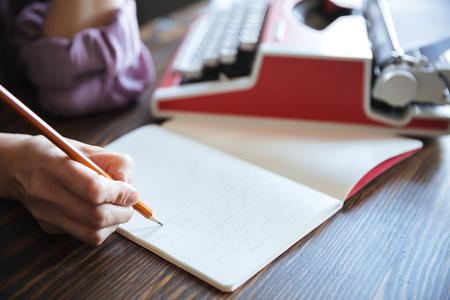 室内のテーブルの上のノートブックを開くに鉛筆を持っている女性手の肖像画間近します。