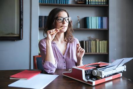 논문 및 타자기 테이블에 앉아 멀리 찾고 안경 잠겨있는 성숙한 사람의 초상화 스톡 콘텐츠
