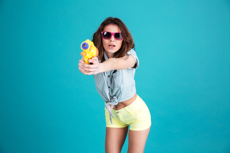 Photo of young smiling woman standing isolated over blue background. Looking at camera holding water gun.