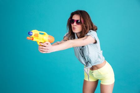 Image of young pretty woman standing isolated over blue background. Looking aside holding water gun.