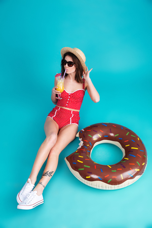 Image of pretty young lady dressed in swimwear wearing sunglasses and hat sitting on floor isolated over blue background while drinking juice.