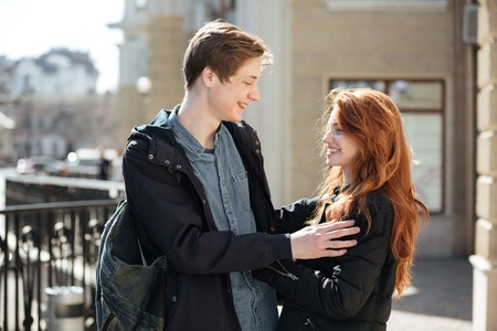 smiing: Cheerful couple of young cute students hugging in the street