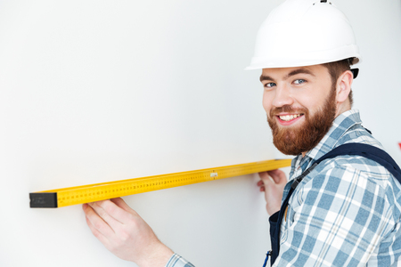 Image of young man builder standing indoors in new flat and make repair. Looking at camera.