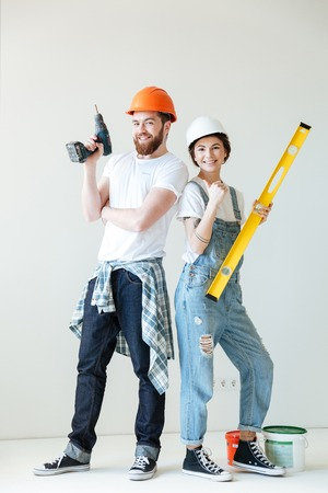 Full length portrait of a young smiling positive couple wearing hardhats and holding tools over white