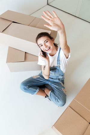 Young smiling talking on phone and waving hand near boxes Stock Photo