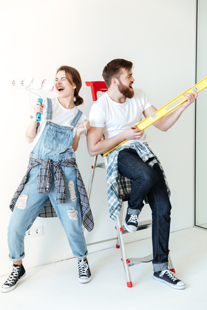 Full length portrait of a happy joyful couple holding work tools and having fun while having a break in repairing their house Standard-Bild