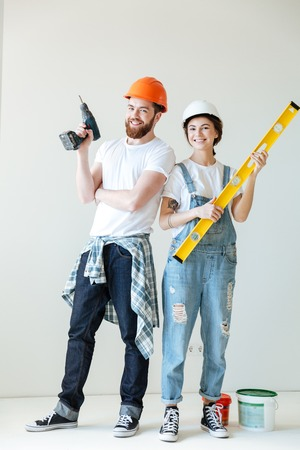 Full length portrait of a smiling happy couple wearing hardhats and holding tools over white Foto de archivo