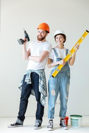 Volledig lengteportret van een glimlachend gelukkig paar die bouwvakkers dragen en hulpmiddelen over wit houden