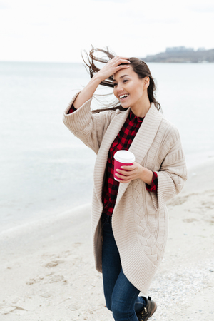 Photo of amazing young caucasian lady walking outdoors at beach wearing warm jacket drinking coffee. Looking aside. Imagens